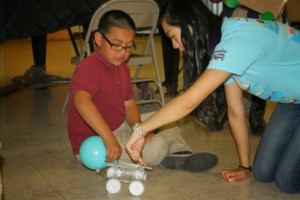 Jessica Chen teaching a child about Newton's Laws.