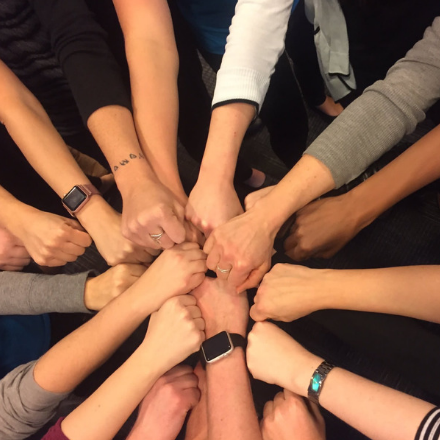 A group of people reach their arms into the center of a circle in a show of teamwork