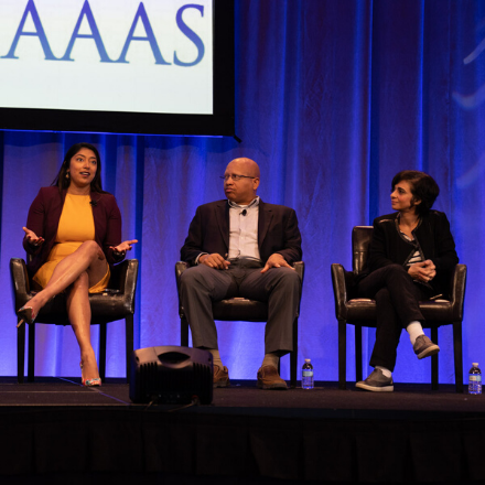 Three panelists sit on a stage in front of the AAAS logo