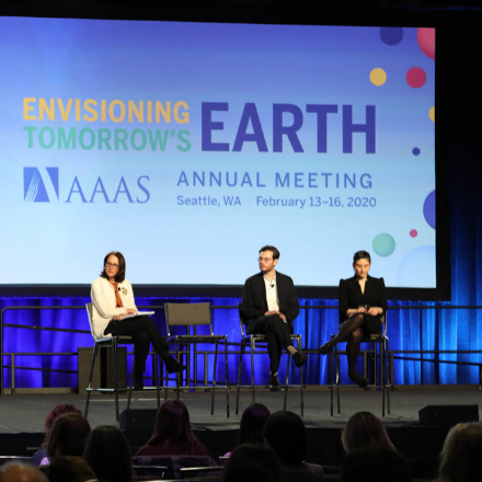 Three people sit on stage in front of a AAAS Annual Meeting logo