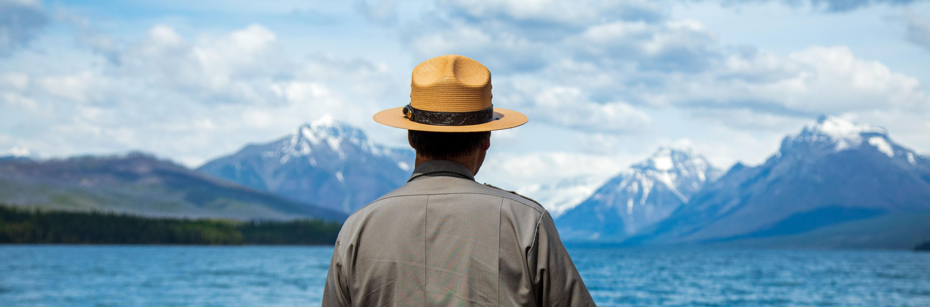 A man wearing a national park ranger hat looks out over a lake with snow-capped mountains in the background.