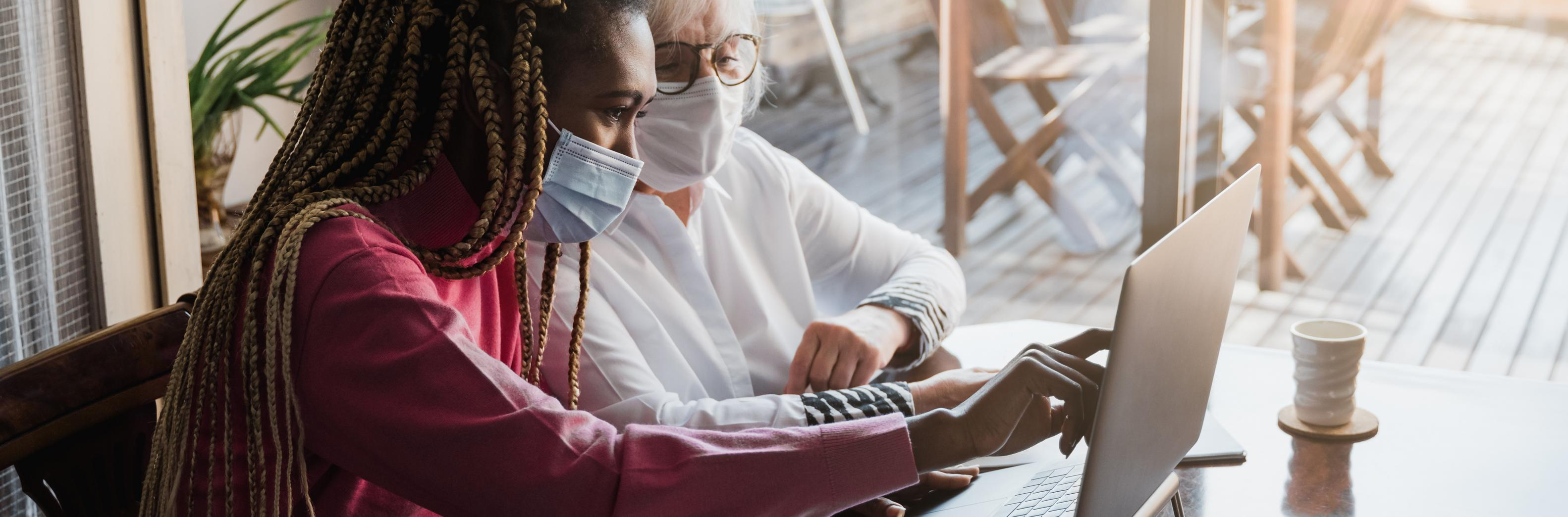 A dark-skinned woman with long brown hair and wearing a red long-sleeved shirt points to a laptop screen while a light-skinned woman with gray hair in a white, long-sleeved shirt watches. Both are wearing masks. Credit: Adobe Stock.