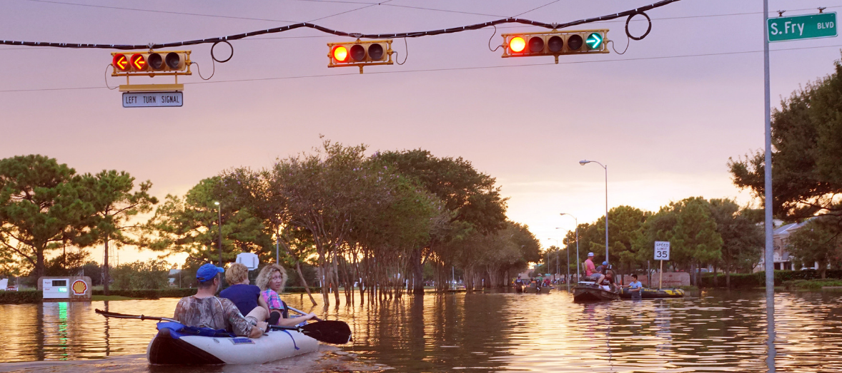 Three people paddle a inflatable boat through a flooded intersection under streetlights, with other boats in the background