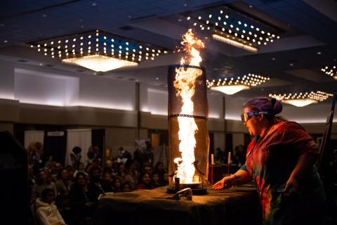 Woman with tower of fire in front of audience