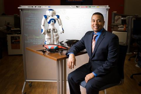 Image of computer science professor sitting by robot and drone.