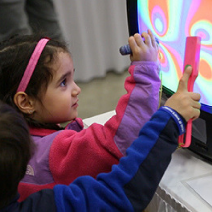 A girl in pink holds a stylus up to a screen showing a multicolored pattern