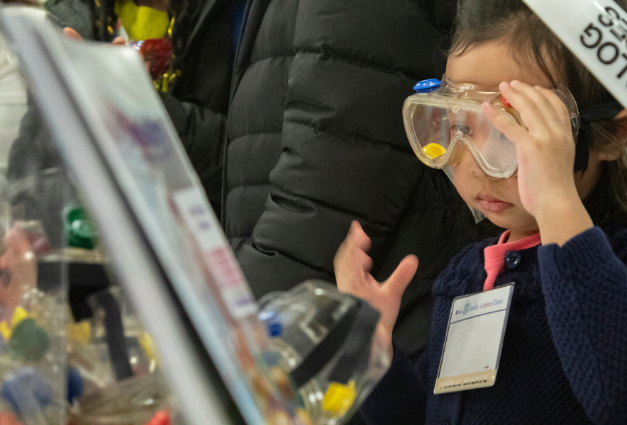 A young girl wearing lab goggles
