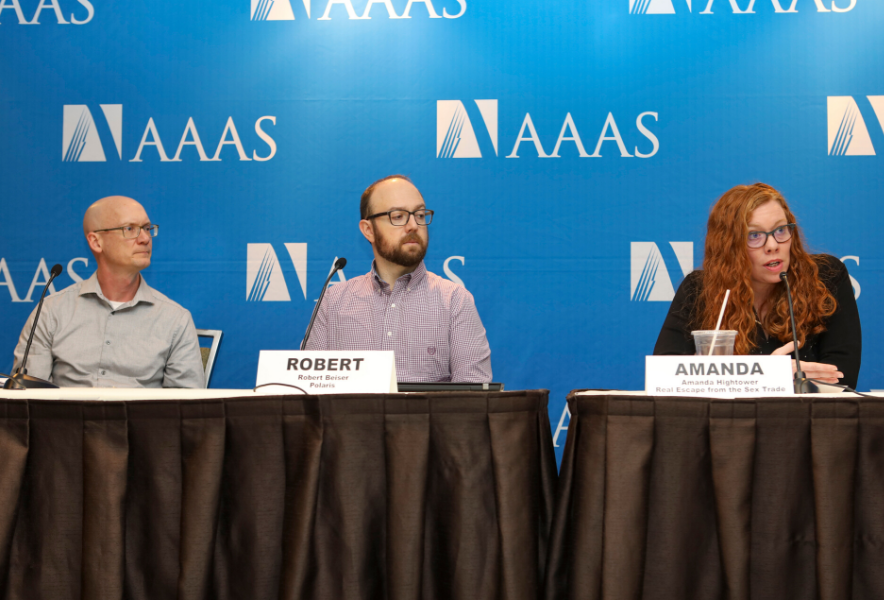 Three people sit before microphones in front of a blue AAAS backdrop