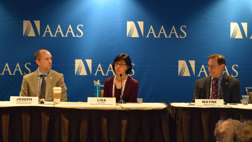 Three scientists sit before microphones in front of a blue AAAS backdrop