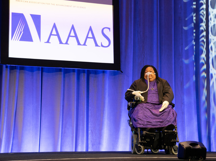 A woman in purple sits in a wheelchair on stage in front of the AAAS logo