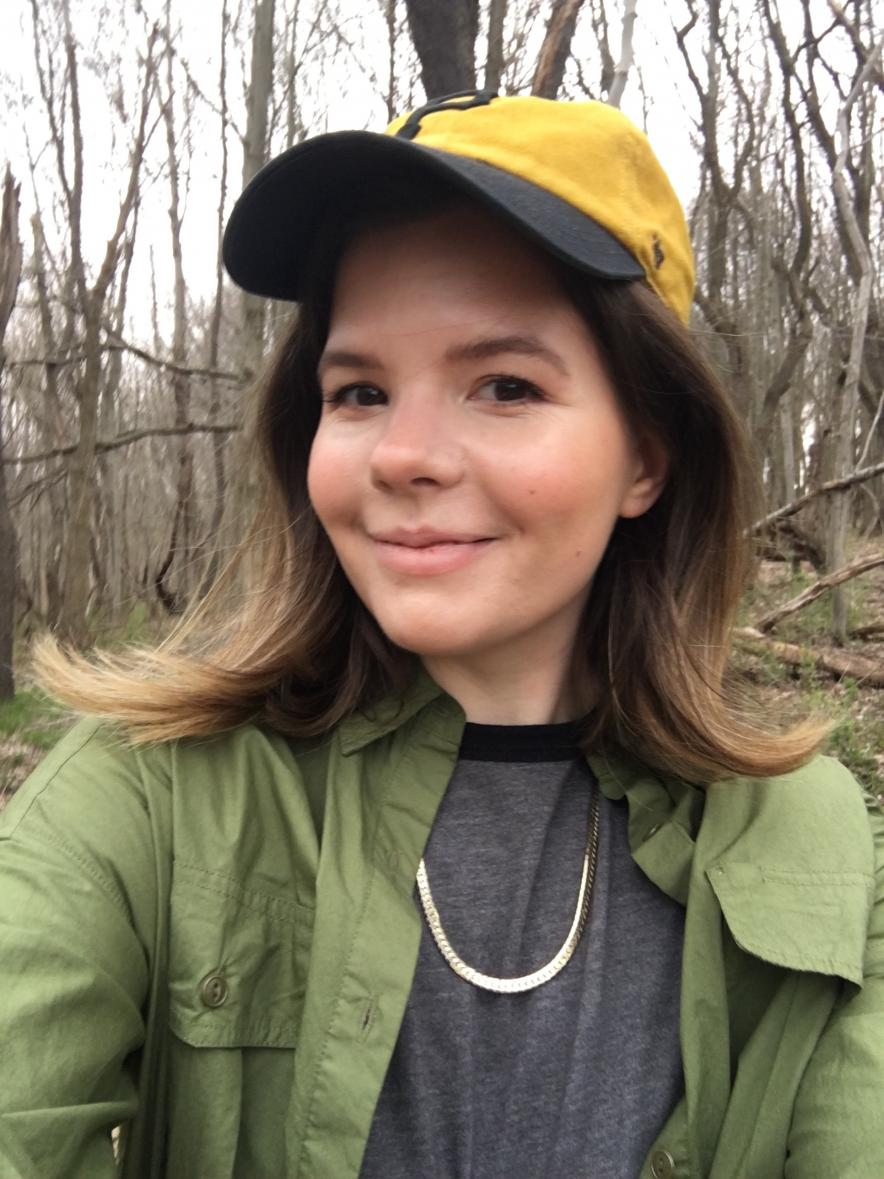 Ana Gorelova wears a yellow hat and a green jacket in a brown forest.