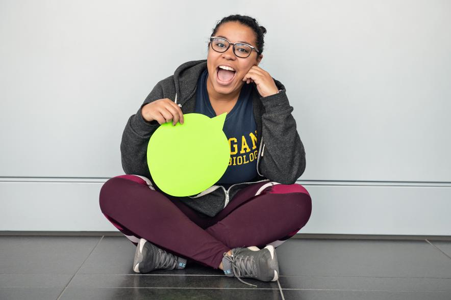 Attabey Rodríguez Benítez sits on the floor, holding a green paper speech bubble in front of her.