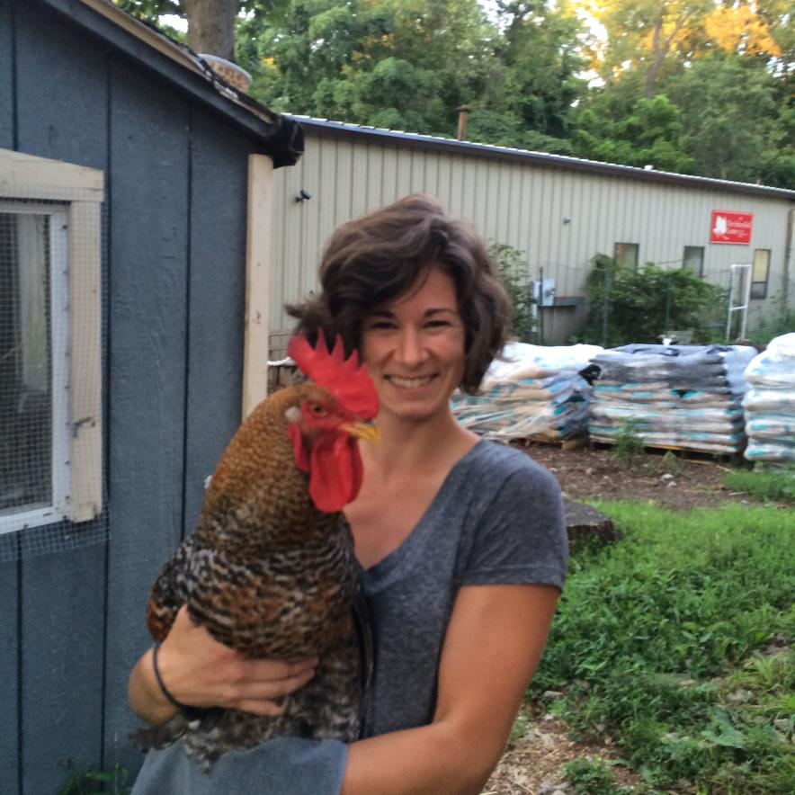 Kelly Franklin holding a rooster while standing next to a shed