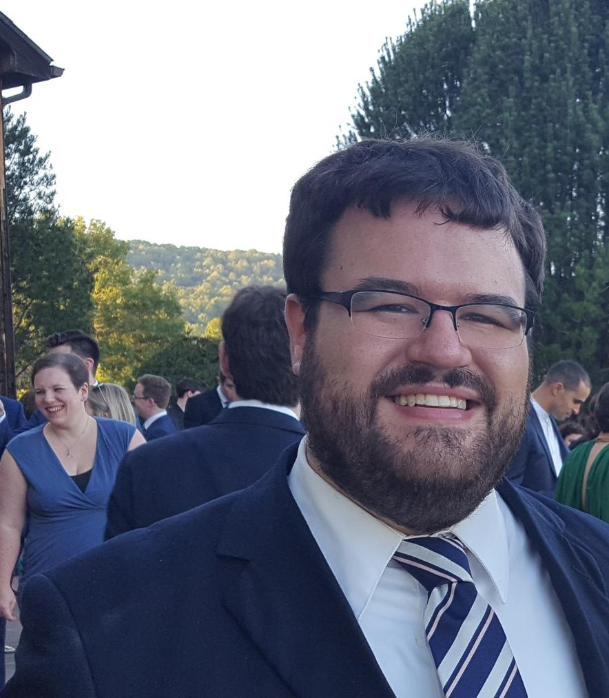 Matthew Diasio wears a suit with people and a green landscape in the background.