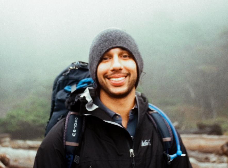 Rishi Sugla smiles while wearing a gray knit cap and a hiking backpack outdoors.