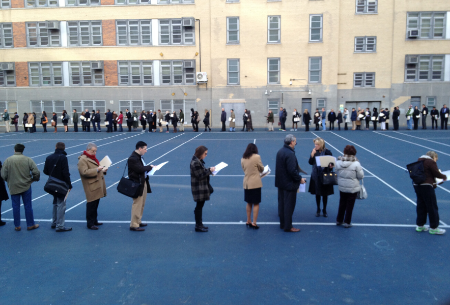 People wait in a long line on a tennis court