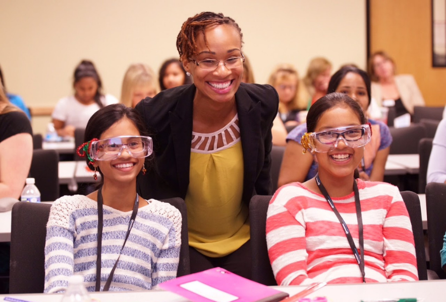 A smiling woman is flanked by two smiling girls wearing lab goggles and striped shirts