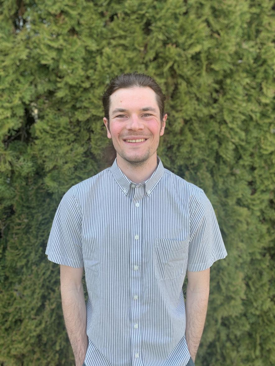 Aaron Anderson smiles at the camera in front of a green hedge. He is wearing a light blue striped button down shirt.