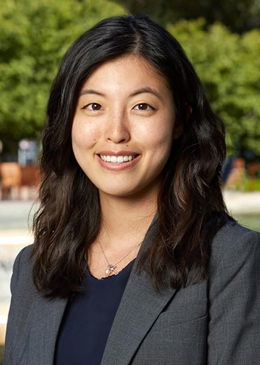 A headshot of Adela Wu wearing a blazer with her hair in front of her shoulders. She's smiling at the camera and there is greenery in the background.