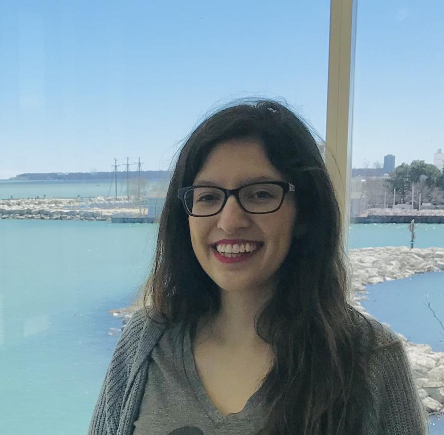 Alejandra Canales smiles at the camera in front of a window overlooking a coastal area. She has long dark hair, glasses, and is wearing a grey sweater over a grey shirt.