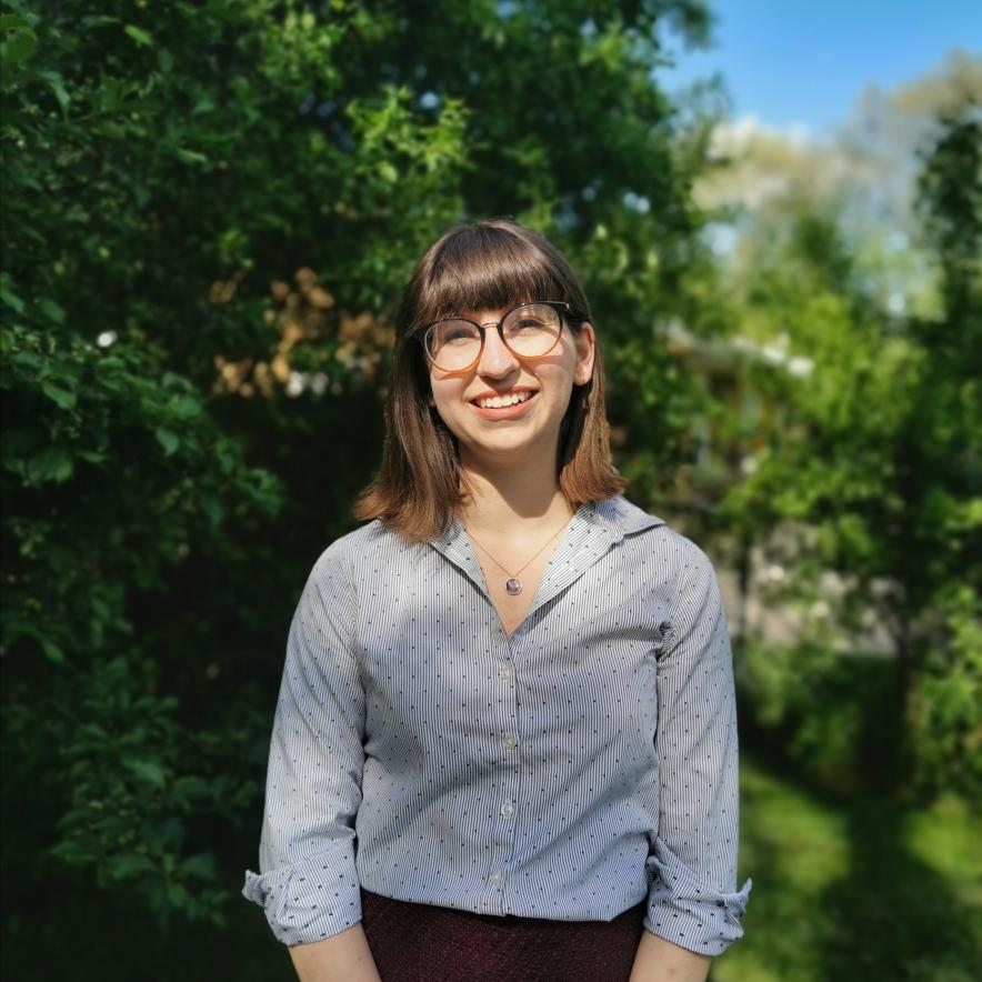 Brianna Barbu tilts her head slightly to her right and smiles at the camera in front of a background of greenery. She's wearing a lightly blue button down shirt, a necklace, and glasses. She has shoulder length hair.