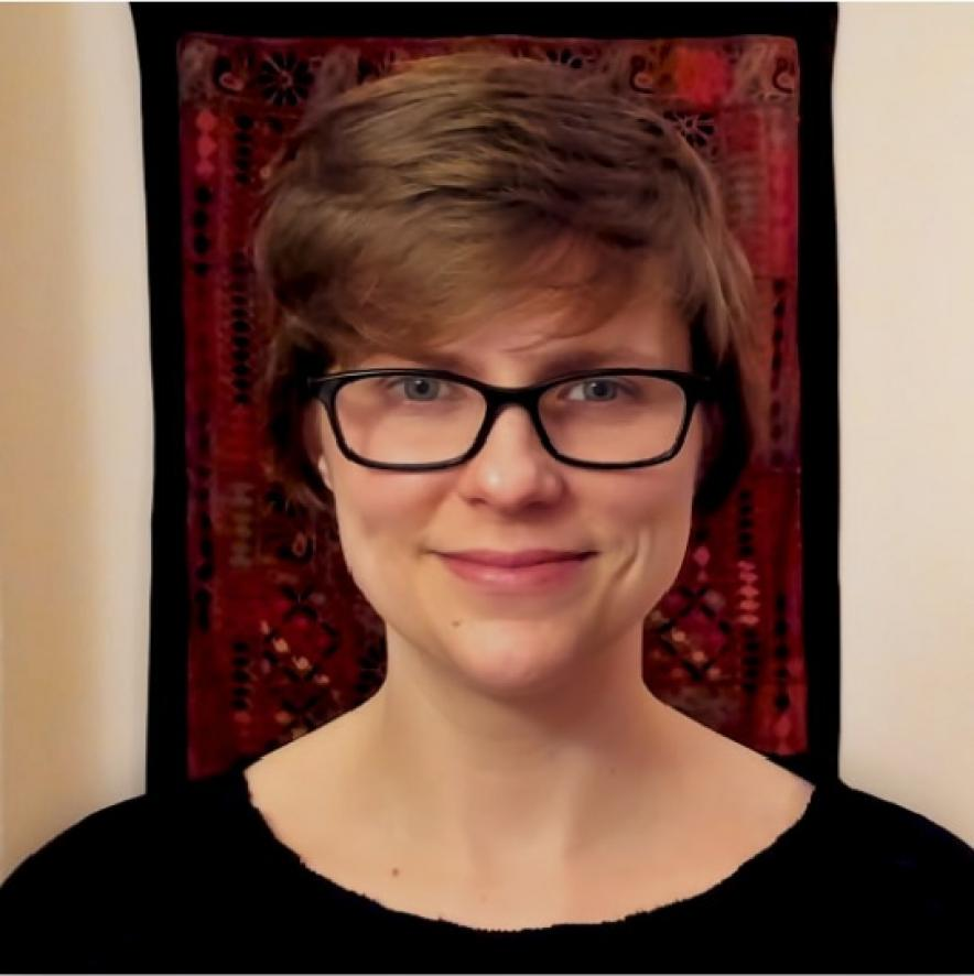 Jennifer Schmidt (a woman with short brown hair and glasses) smiles at the camera in front of a red, patterned fabric.