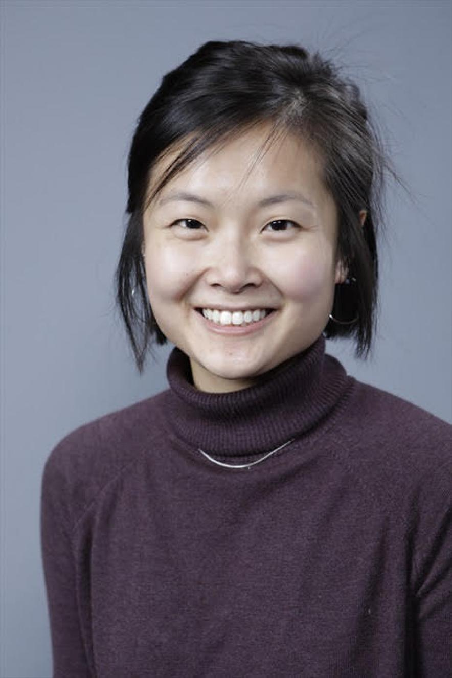 Luyi Cheng smiles at the camera with short black hair, a dark turtleneck sweater and hoop earrings. She's in front of a blue-gray background.