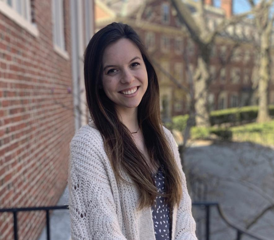 Madison Goldberg smiles at the camera, with long hair in front of her shoulders. She has a white sweater and appears to be in a courtyard on a campus.
