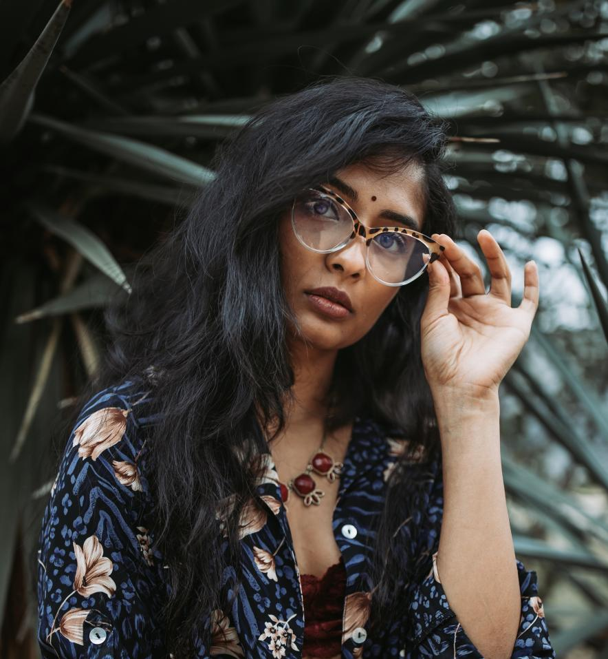 Niba Audrey Nirmal tilts her head, holding her glasses and looks at the camera. She's in front a dark green palm-like plant and wearing a blue floral shirt.