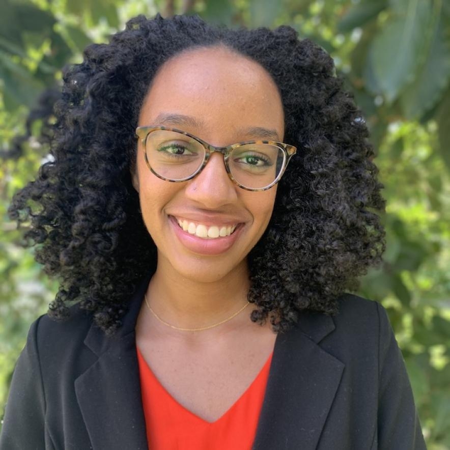 Priya Dames has tortoise-shell glasses, curly black hair, and is smiling at the camera in front of a blurred background of greenery. She's wearing a red top and dark blazer.