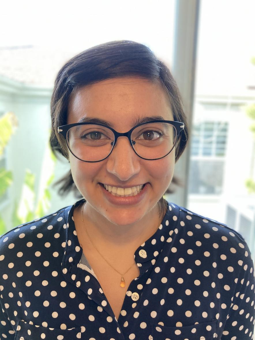 Sophia Charan smiles at the camera in front of a window. Her short brown hair is pulled back and she's wearing glasses and a blue polka-dotted shirt.
