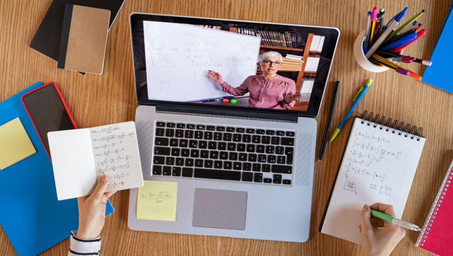 An overhead photo of an open laptop on a desk, next to a person's hand writing in a notepad