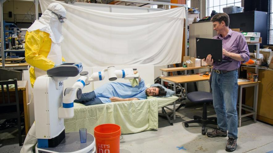 Graduate students Austin Whitesell and Alan Sanchez and Bill Smart, professor of robotics, demonstrate an experiment simulating how robots might be used during Ebola outbreaks.
