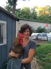 Kelly Franklin holding a rooster and smiling.