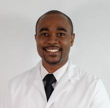 Adewole Adamson, M.D, M.P.P. smiles wearing a white lab coat.