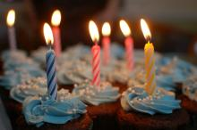 Cupcakes with lit birthday candles in each