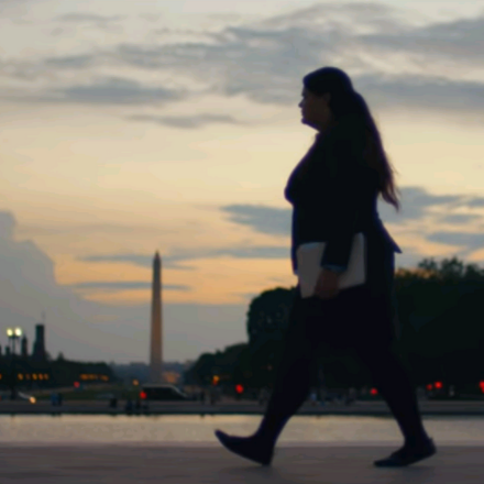 A woman walks past the Washington Monument at sunset