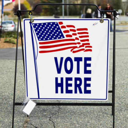"A sign that reads ""Vote Here"" with an American flag illustration"