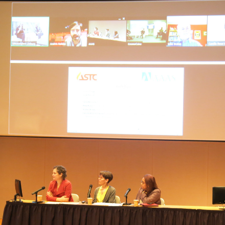 Three women on stage behind a table below a video screen showing other panel participants