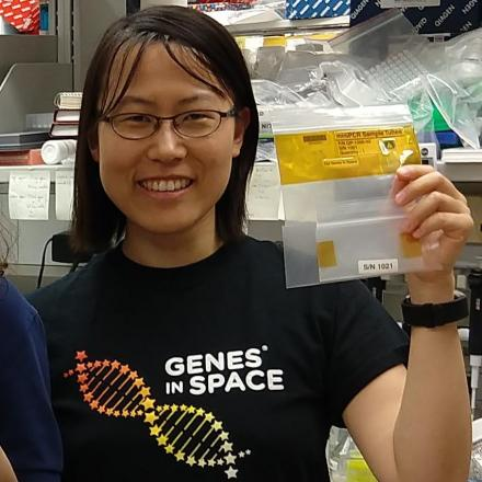 "Diana Cai holds PCR tubes in a science lab wearing a t-shirt with ""Genes in Space"" written on it."