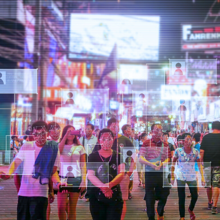 Facial recognition imagery is laid over people walking down a busy street