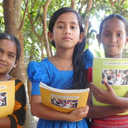 Three children holding schoolbooks. Photo copyright 2017 CARE Tipping Point Photovoice.