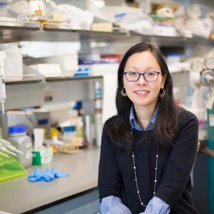 Dr. Jin Kim Montclare seated a bench in her lab