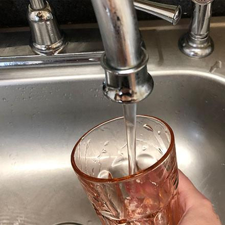 A glass is held under a kitchen faucet