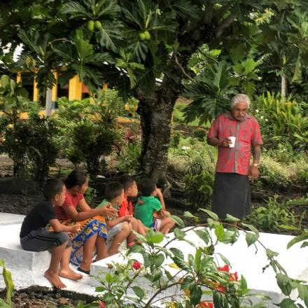 master hand-tap tattooist Su'a Sulu'ape Petelo Alaiva'a at the gravesite of his father, Su'a Paulo Sulu'ape, talking to his grandchildren about their heritage as preservers of traditional tattoo knowledge