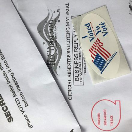 A mail in ballot and 'I voted' sticker