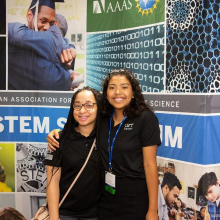Two girls in front of S-STEM poster
