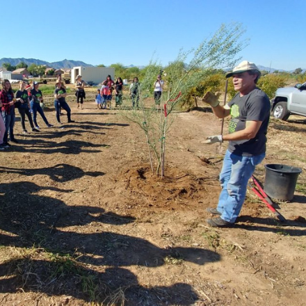 Volunteers are briefed on best practices for tree planting from a professional arborist, ahead of a community greening event along the Salt River in Phoenix, AZ.