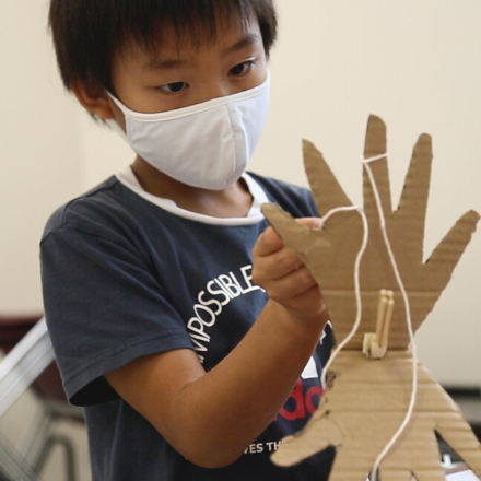 A boy in a face mask holding a cardboard cutout of a hand